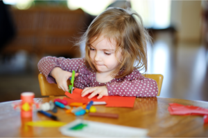 child cutting colored paper